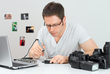 Photographer soldering wireless flash trigger at his workplace.
