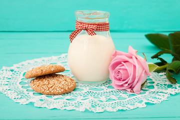 Breakfast with a jug of milk and cookies. Pink rose and lace napkin on wooden table.