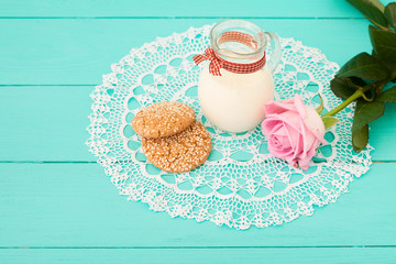 Breakfast with jug of milk and cookies near rose on lace napkin. Wooden background