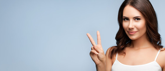 Woman showing two fingers or victory gesture, with copyspace