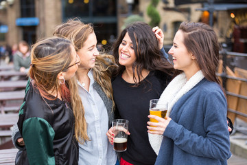 Group of women enjoying a beer at pub in London.
