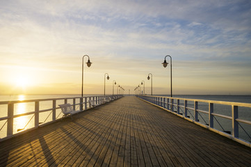 The wooden pier on the sea at sunrise