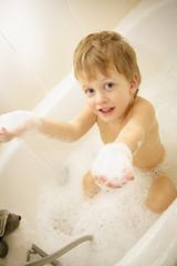 Cute boy taking a bath with foam