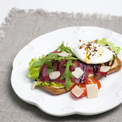 Sandwich with poached eggs and jamon