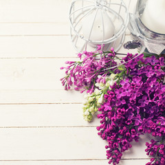 Lilac flowers  and candles on wooden background.
