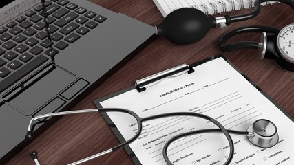 Laptop with medical instruments and patient form on desktop