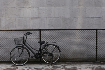 Vintage bicycle with fence and grey wall background
