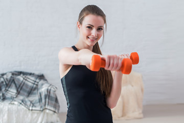 Active sportive athletic woman boxing dumbbells pumping up