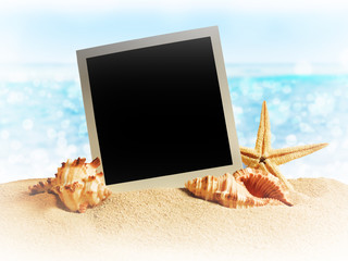 seashells and old photo frame on sand