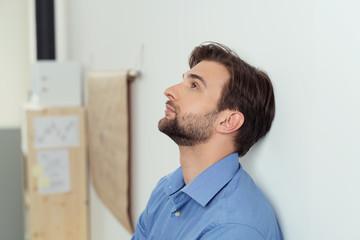 nachdenklicher mann lehnt an der wand im büro