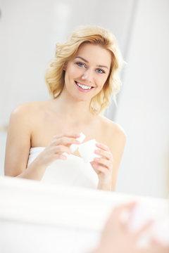 Woman putting on cream in bathroom