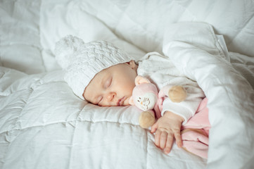 sweet small baby sleeps with a toy cat in a white hat