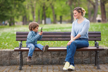 Cute little boy photographing his mother sitting on a park bench