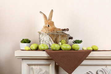 Cute red rabbit with Easter eggs on shelf on light wallpaper background