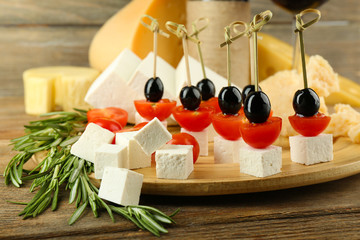 Cheese canapes with with rosemary on table close up