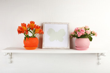 Beautiful flowers in pots on shelf on wall background