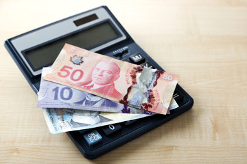 Calculator and Canadian dollars, on wooden table