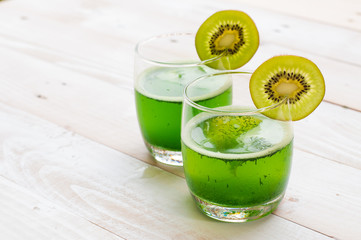 kiwi smoothie in glass on a old white wooden background