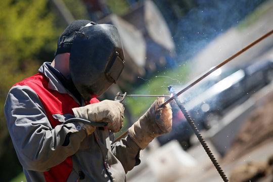 Construction worker welder welding steel rod rebar outdoors