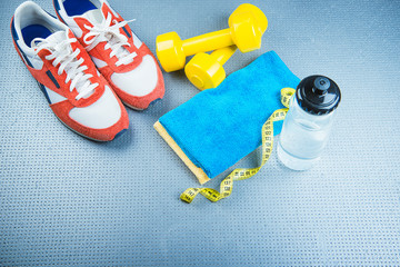 Sneakers and dumbbells fitness on a gray background.