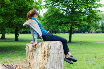 Young woman sitting on tree trunk in park