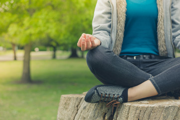 Young woman meditating on tree trunk in park