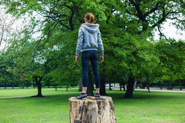 Young woman standing on a tree trunk in park