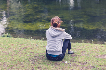 Woman sitting by water in the park