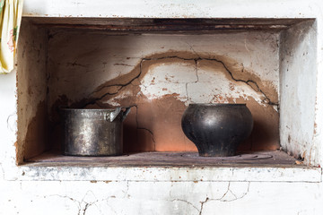 Old dishes on the old furnace. Vintage toning