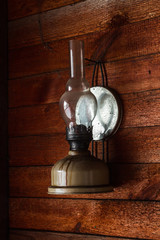 Kerosene lamp on a wooden wall. Vintage toning