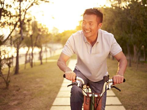 asian man enjoying bike riding outdoor in park at sunset