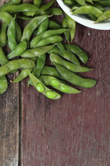 Edamame soy beans on wood background.
