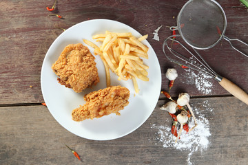 fried chicken wings with french fries on wood table. view from a