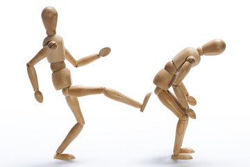 Wooden mannequin kicking in the backside to other