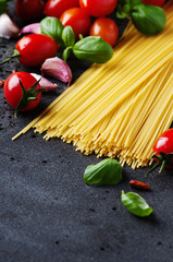 Uncooked spaghetti with tomato and basil