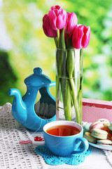 Composition of spring flowers, tea and cookies on table on natural background