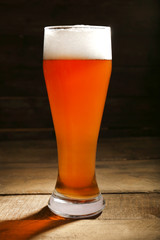 Glass of beer on wooden table on dark background