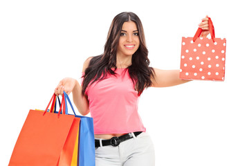 Trendy girl holding shopping bags isolated on white