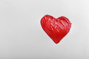 Painted red heart on white paper background