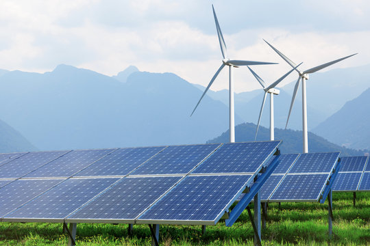 solar panels and wind turbines against mountains