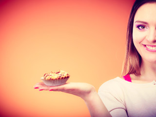 Smiling woman holds cake in hand