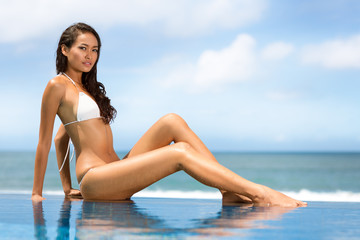 woman in swimsuit sitting in front of swimming pool in gorgeous