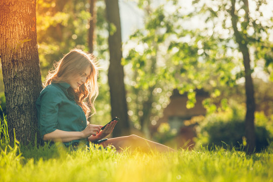 Pretty young caucasian woman  sitting outside under a tree