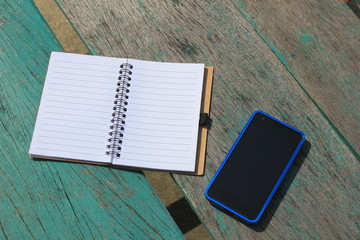 notebook and mobile phone on the green table