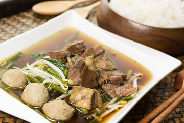 Stewed beef soup with rice on wood tray