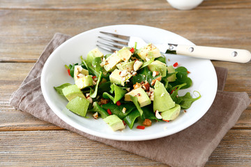 Salad with avocado, spinach and nuts in a bowl