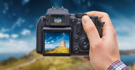 DSLR camera in hand shooting landscape with watchtower