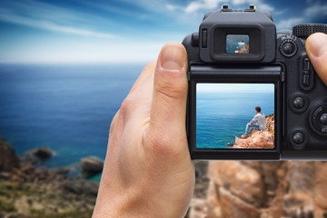 DSLR camera in hand shooting solitary man on top of the coast