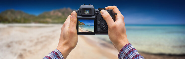 DSLR camera in hands shooting seascape