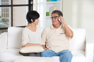 asian senior couple having phone conversation